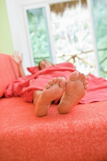 woman sleeping with feet out from covers : Stock Photo