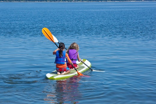 girls on paddle board in lake : Stock Photo