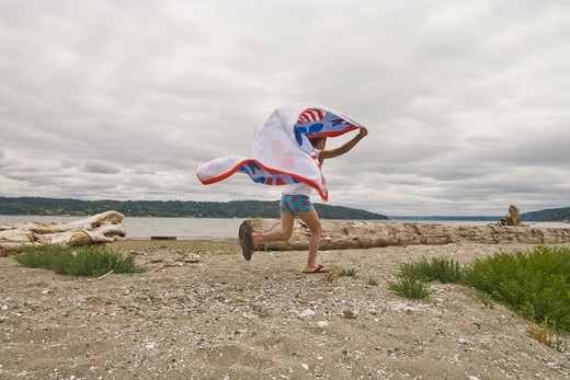 boy running on beach with flying towel : Stock Photo