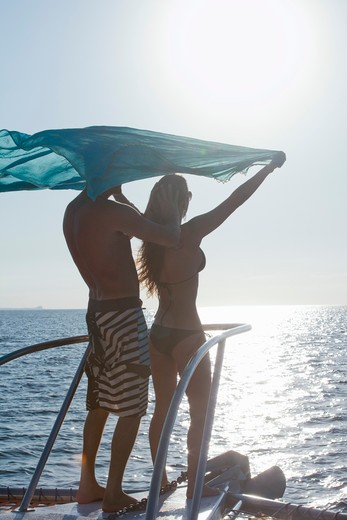 couple on bow of yacht with flying sari : Stock Photo