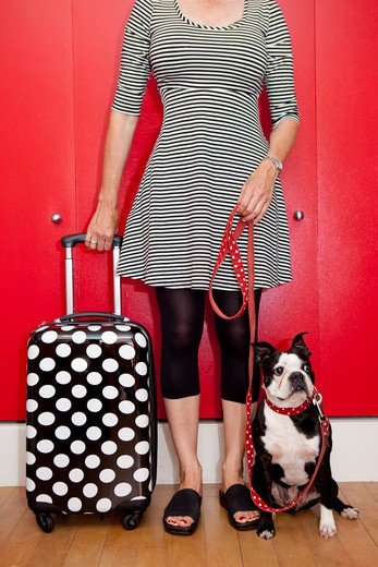 Stock Photo: 1530R-41624 Woman with polka dot suitcase and dog on leash