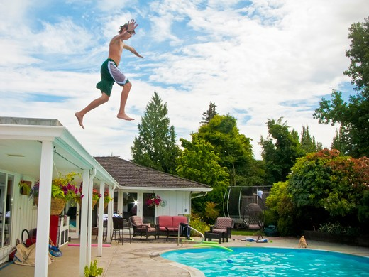 Teen boy jumping off roof into pool : Stock Photo