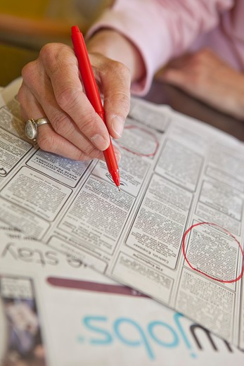 Woman circling employment ads in paper, : Stock Photo