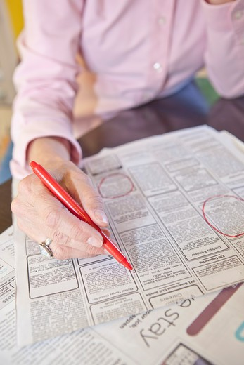 Stock Photo: 1530R-41688 Woman circling employment ads in paper,