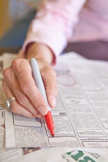 Stock Photo: 1530R-41689 Woman circling employment ads in paper,