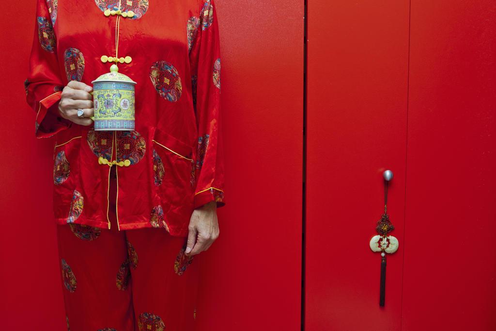 Stock Photo: 1530R-41700 Woman wearing red silk Chinese pajamas,