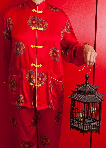 Stock Photo: 1530R-41701 Woman wearing red silk Chinese pajamas,