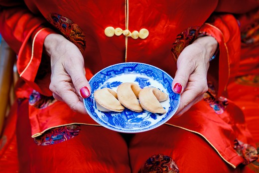 Stock Photo: 1530R-41706 Woman holding plate of fortune cookies,
