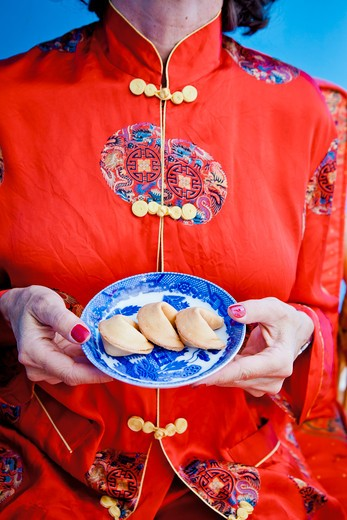 Stock Photo: 1530R-41707 Woman holding plate of fortune cookies,