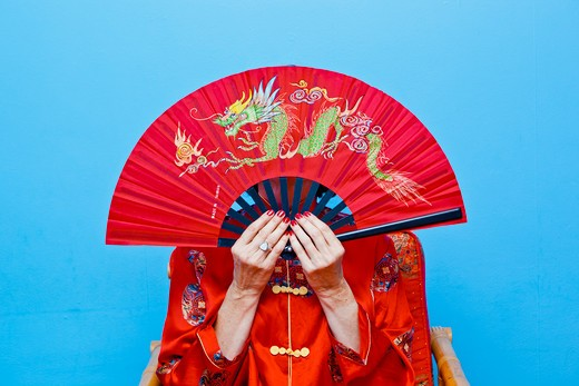 Woman holding red fan in front of her face, : Stock Photo
