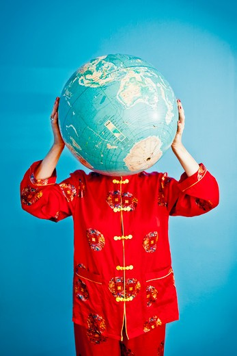 Stock Photo: 1530R-41717 Woman in Chinese pajamas holding globe,