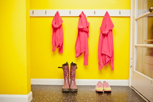 Stock Photo: 1530R-41731 Sweaters on hooks with boots and shoes below,