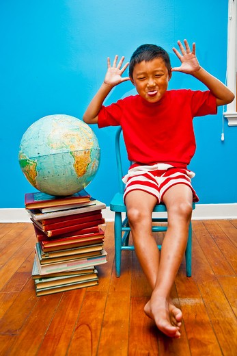 Stock Photo: 1530R-41737 Boy making face next to books and globe,