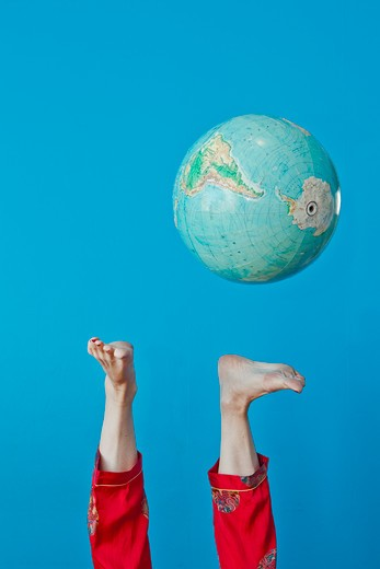 Feet kicking globe in air, : Stock Photo