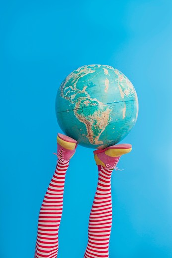Stock Photo: 1530R-41746 Legs in striped socks with colorful shoes holding globe,
