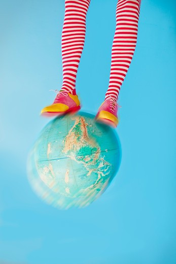Legs in striped socks with colorful shoes on globe, : Stock Photo