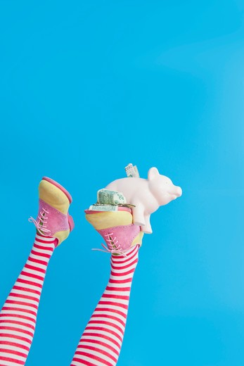 Stock Photo: 1530R-41748 Legs in striped socks with colorful shoes holding piggy bank,