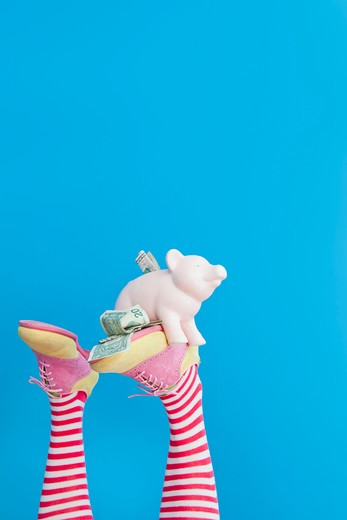 Stock Photo: 1530R-41749 Legs in striped socks with colorful shoes holding piggy bank,