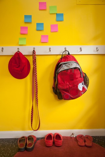 Stock Photo: 1530R-41758 Yellow wall with colorful post-its and loaded coat hooks,