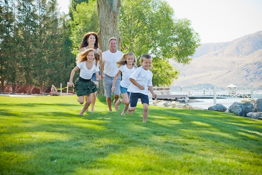 Stock Photo: 1530R-41774 Family of five running in lakeside park,
