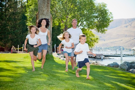 Stock Photo: 1530R-41777 Family of five running in lakeside park,