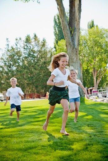 Stock Photo: 1530R-41784 Three young children running in park,
