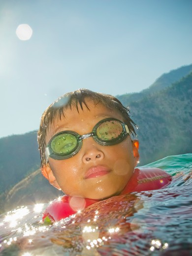Boy coming up out of water, : Stock Photo