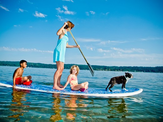 Stock Photo: 1530R-41793 Woman on paddle board with kids and dog,