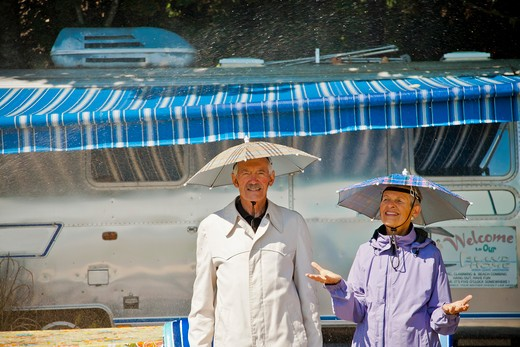 Stock Photo: 1530R-41803 Senior couple in rain hats near airstream camper,