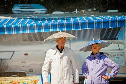 Stock Photo: 1530R-41804 Senior couple in rain hats near airstream camper,