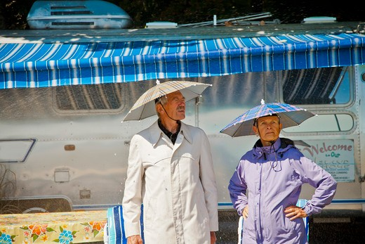 Senior couple in rain hats near airstream camper, : Stock Photo