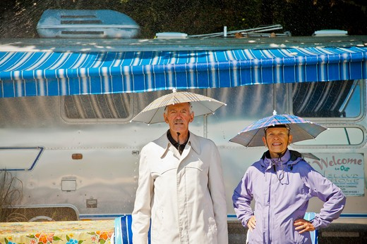 Stock Photo: 1530R-41806 Senior couple in rain hats near airstream camper,