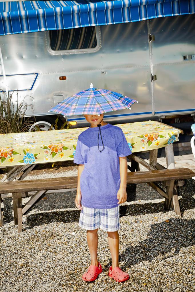 Boy in rain hat near airstream camper, : Stock Photo