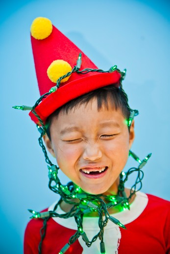 Boy in red costume with holiday lights, : Stock Photo