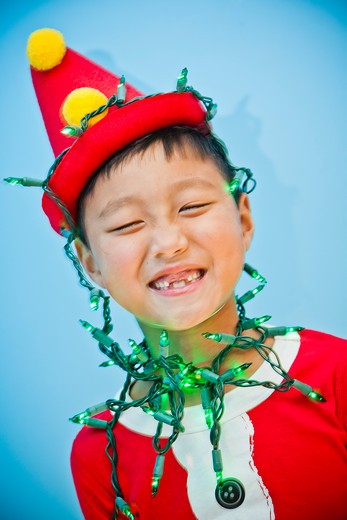 Stock Photo: 1530R-41810 Boy in red costume with holiday lights,
