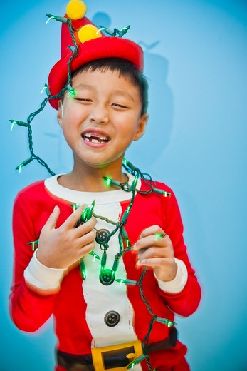 Stock Photo: 1530R-41813 Boy in red costume with holiday lights,