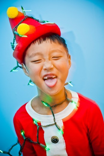 Stock Photo: 1530R-41814 Boy in red costume with holiday lights,