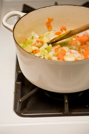 White pot with vegetables on stove, : Stock Photo