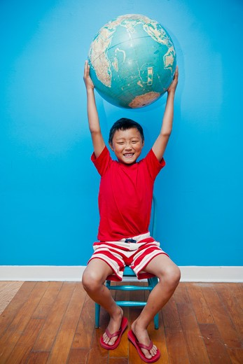 Seated boy holding globe, : Stock Photo