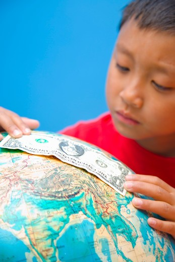 Stock Photo: 1530R-41820 Boy placing dollar bill on globe,