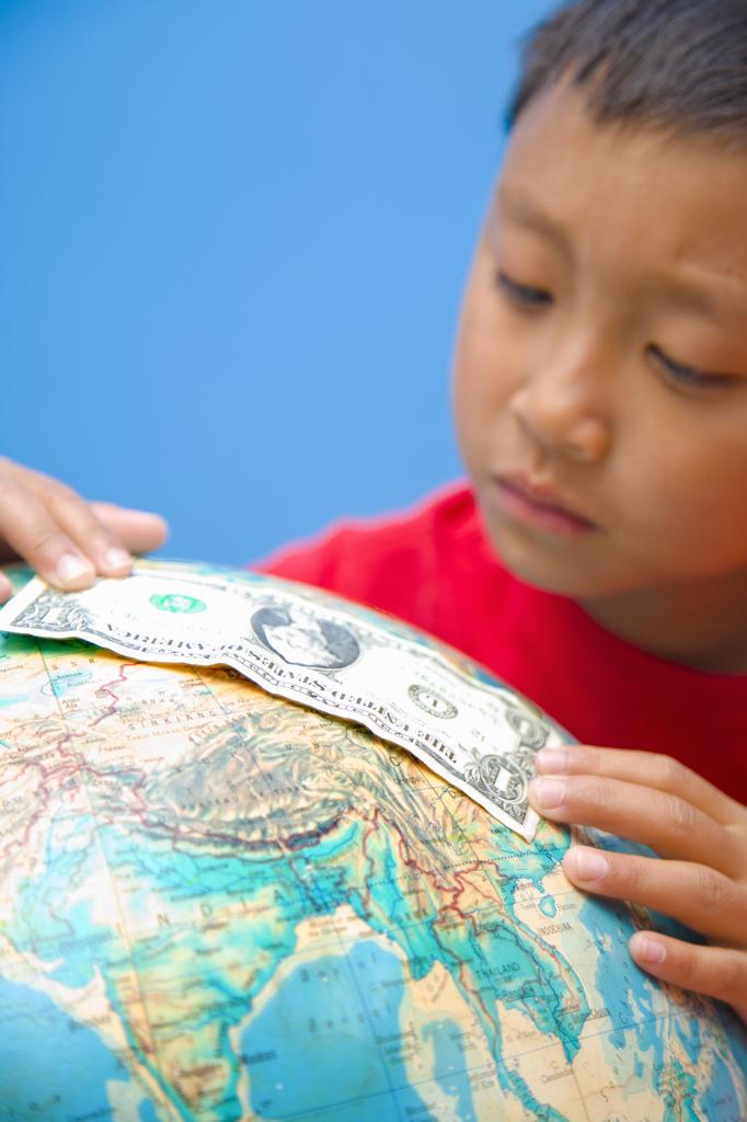 Boy placing dollar bill on globe, : Stock Photo
