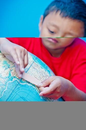 Stock Photo: 1530R-41822 Boy placing bandaid on globe,