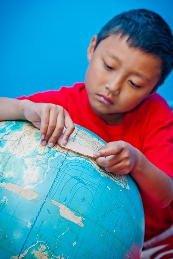 Boy placing bandaid on globe, : Stock Photo