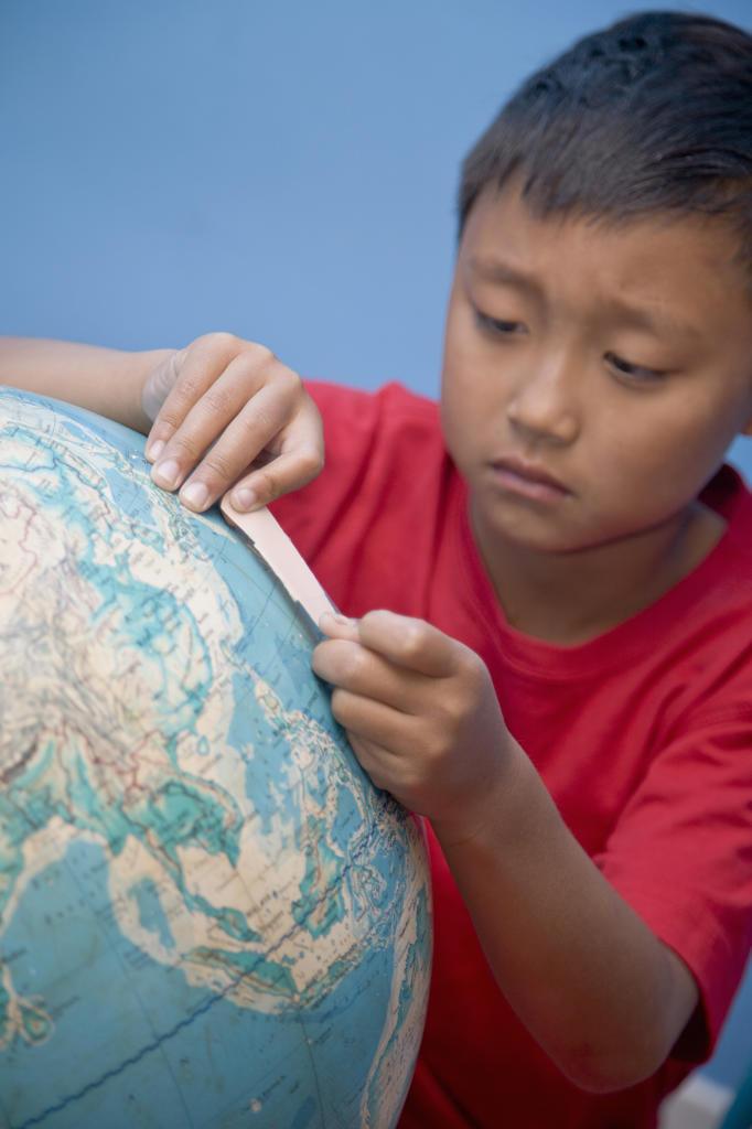 Stock Photo: 1530R-41824 Boy placing bandaid on globe,