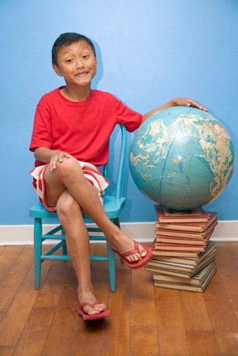 Boy seated next to globe resting on stack of books, : Stock Photo