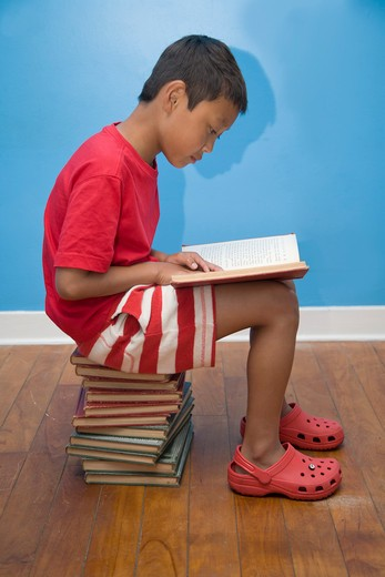 Boy reading while seated on stack of books, : Stock Photo