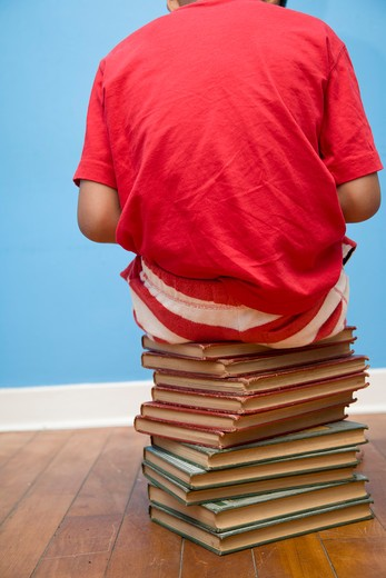 Rear view of boy sitting on stack of books, : Stock Photo