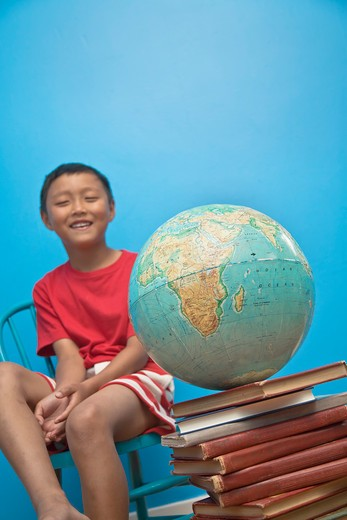 Boy seated near globe on top of books, : Stock Photo