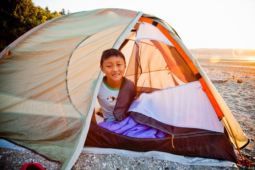 Stock Photo: 1530R-41848 Young boy peeking out from tent on beach at sunrise,
