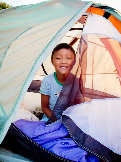 Stock Photo: 1530R-41849 Young boy peeking out from tent on beach at sunrise,